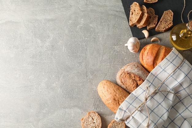 Composição com produtos de panificação, alho, azeite e toalha de cozinha em espaço cinza, vista superior e espaço para texto