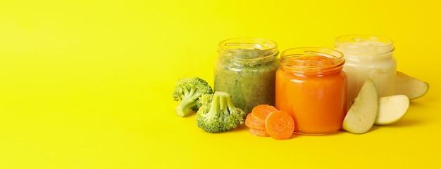 Composição com purê de legumes em fundo amarelo. comida de bêbe