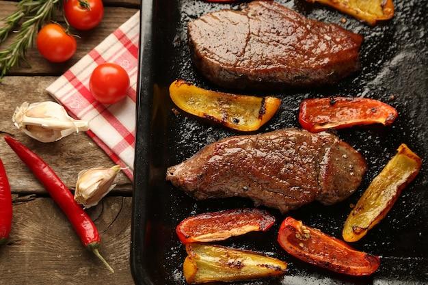 Composição com saborosa carne assada e pimenta fatiada na frigideira, tomate e raminhos de alecrim na madeira