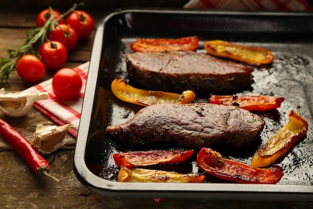 Composição com saborosa carne assada e pimenta fatiada na frigideira, tomate e raminhos de alecrim na mesa de madeira