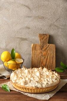 Composição com saborosa torta de limão e merengue na mesa de madeira