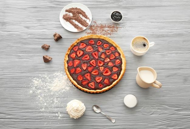 Composição com saboroso bolo de chocolate na mesa de madeira