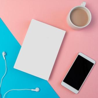 Composição com smartphone, fones de ouvido, bloco de notas e xícara de café