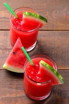 Composição com smoothies de melancia e fatias de melancia fresca em uma mesa de madeira marrom