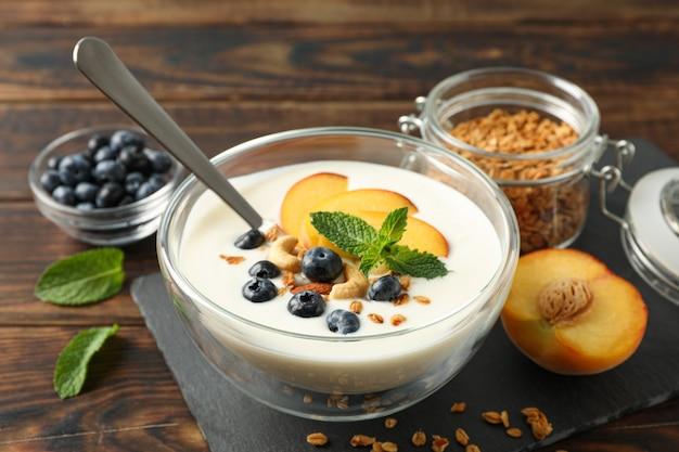 Composição com sobremesa de iogurte e ingredientes em fundo de madeira