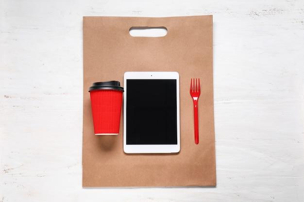 Composição com tablet pc e café na mesa de madeira. vista do topo