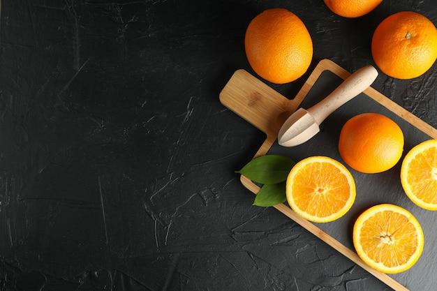 Composição com tábua, laranjas e espremedor de frutas de madeira. vista superior, espaço para texto