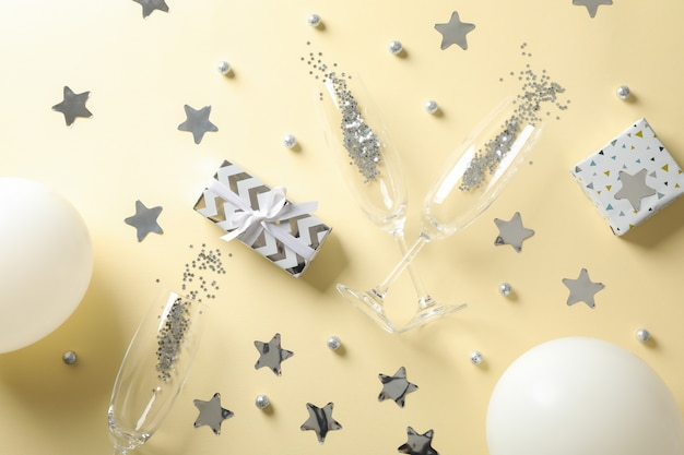 Composição com taças de champanhe, presentes e glitter em bege, vista superior