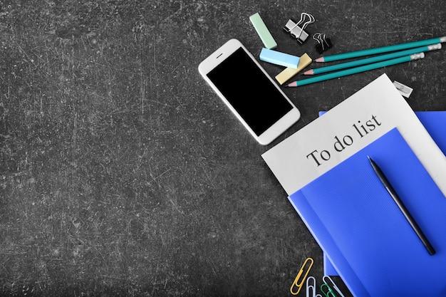 Composição com telefone celular e lista de tarefas em fundo cinza
