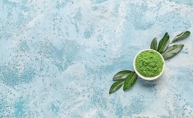 Composição com tigela de chá matcha em pó e folhas frescas na cor de fundo