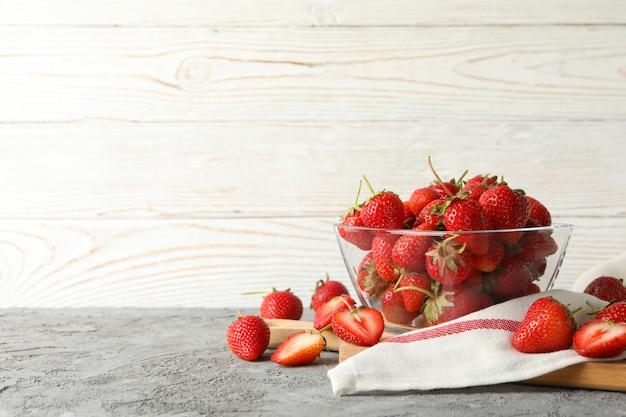Composição com tigela de morango saboroso na mesa cinza. baga de verão