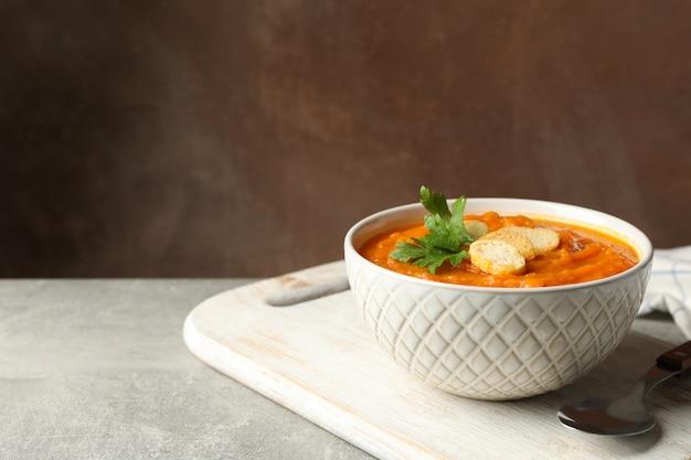 Composição com tigela de purê de abóbora com croutons na mesa cinza