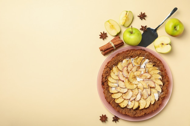 Composição com torta de maçã e ingredientes em fundo bege, vista superior