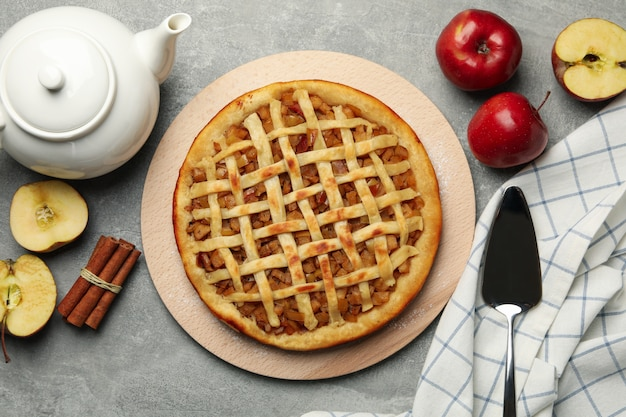 Composição com torta de maçã e ingredientes em fundo cinza, vista superior