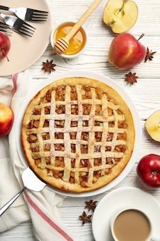 Composição com torta de maçã e ingredientes em fundo de madeira, vista superior