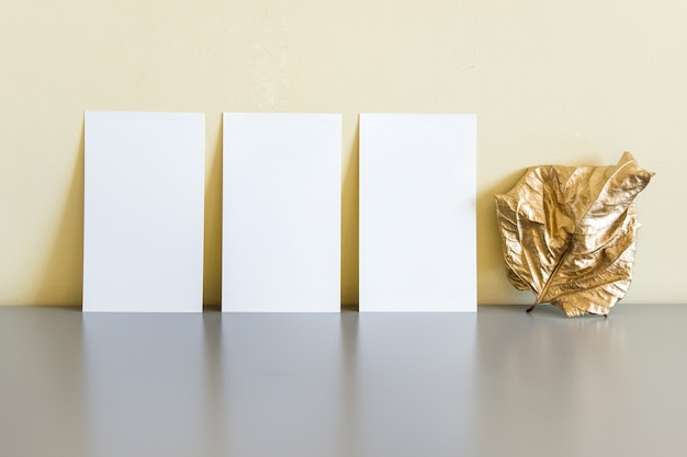 Composição com três cartas e folha seca dourada sobre superfície reflexiva cinza.