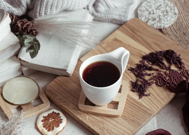 Composição com um copo de bebida quente entre coisinhas lindas. conceito de conforto em casa.