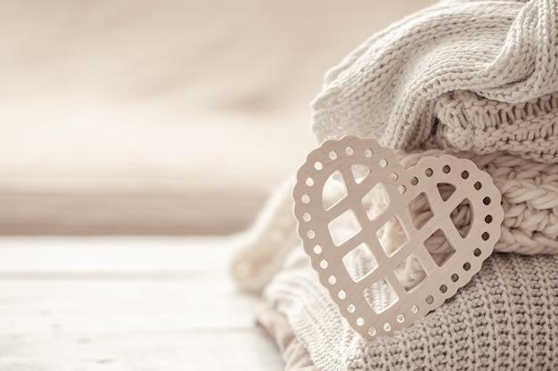 Composição com um coração decorativo no fundo de roupas quentes bem dobradas.