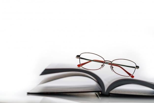 Composição com um livro aberto e óculos em uma parede branca com espaço para texto.