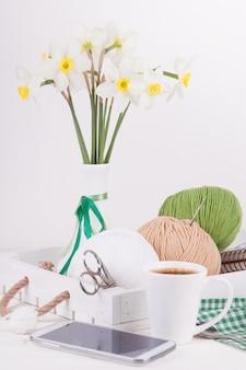 Composição com um vaso e uma bandeja de madeira e bolas do fio para o bordado.