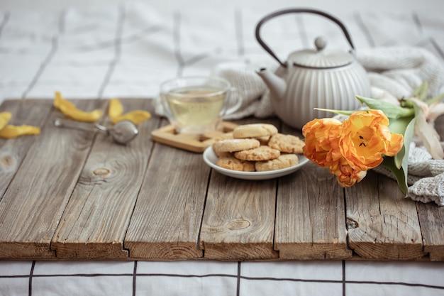 Composição com uma xícara de chá, um bule de chá, biscoitos e um buquê de tulipas