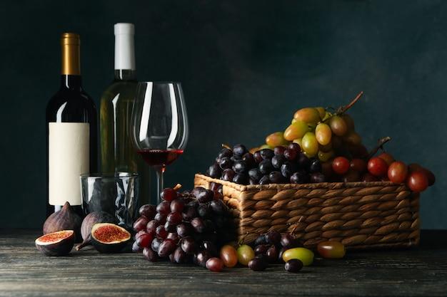 Composição com uva, vinho e figo na mesa de madeira