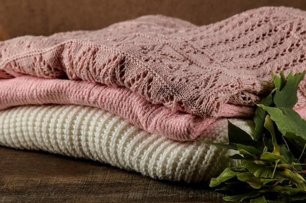 Composição com vários suéteres quentes empilhados em um fundo de madeira marrom