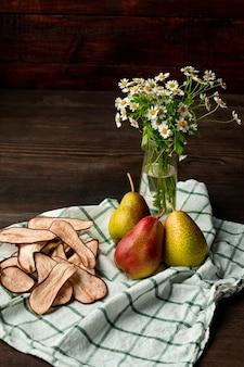 Composição com vaso de flores silvestres, toalha de linho de cozinha, peras maduras e tábua de cortar com fatias de frutas frescas