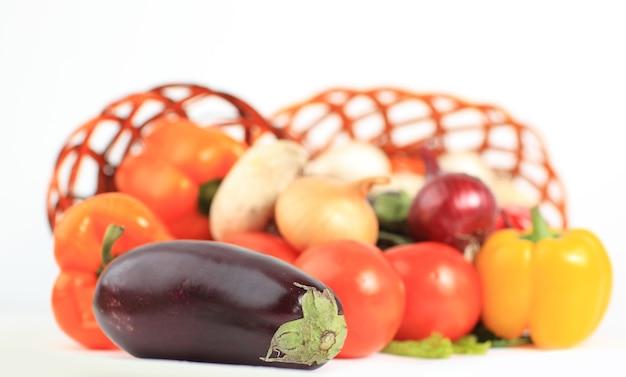 Composição com vegetais crus e cesta de vime isolada no branco