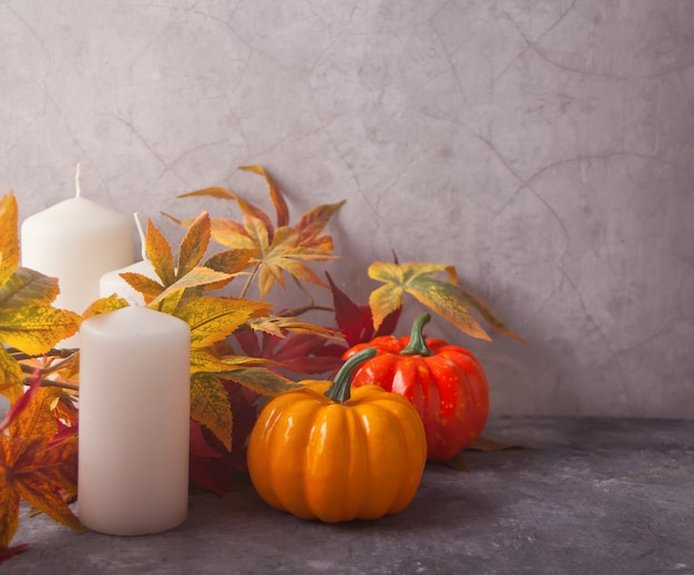 Composição com velas, folhas de outono, abóboras. colheita de outono. conceito de outono. copie o espaço
