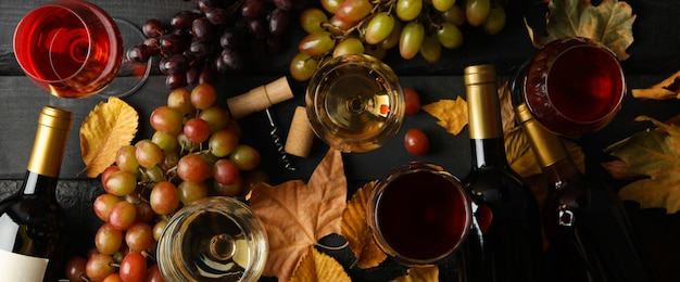 Composição com vinho e uva em fundo de madeira, vista superior