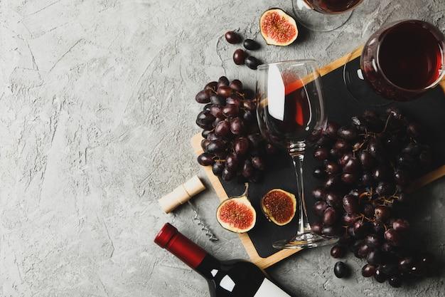 Composição com vinho, uva e figo em fundo cinza