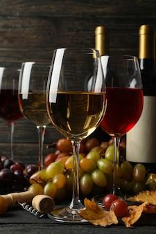 Composição com vinho, uva e folhas em fundo de madeira