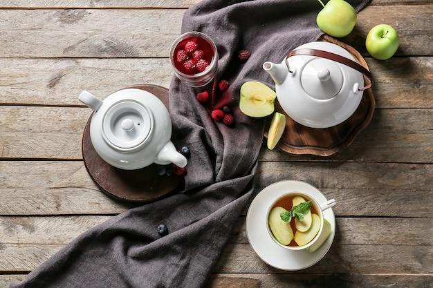 Composição com xícaras de chá quente de frutas em fundo de madeira