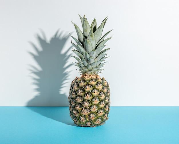 Composição criativa com abacaxi sobre fundo azul.