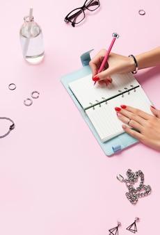 Composição criativa com acessórios de final de planejador de mãos de mulher sobre a mesa rosa