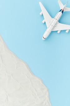 Composição criativa com avião de brinquedo e areia. conceito de viagens de férias