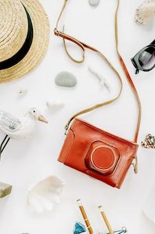 Composição criativa com estatueta de pássaro, barco de brinquedo, câmera retro, óculos de sol, conchas e chapéu de palha na superfície branca