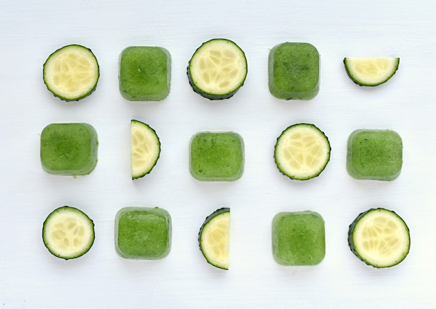 Composição criativa com fatias do pepino e cubos de gelo do suco do pepino para o tratamento da pele.