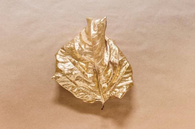 Composição criativa com folha única tingida com cor metálica dourada sobre superfície de papel kraft
