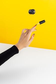 Composição criativa com mãos de mulher e esmalte voador