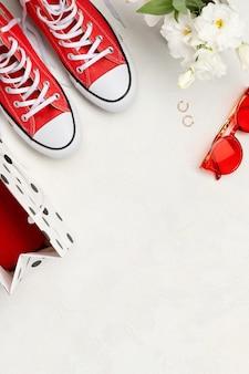 Composição criativa com tênis vermelhos, cosméticos e acessórios