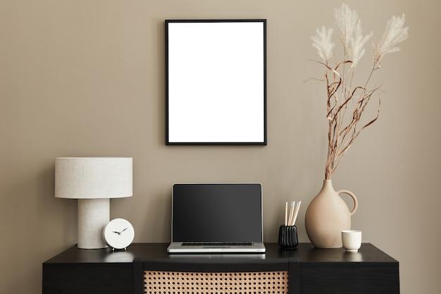 Composição criativa de design de interiores de espaço de trabalho em casa elegante com moldura, mesa, laptop, planta em vaso de design rústico e acessórios. conceitos minimaslíticos ..