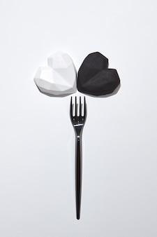 Composição criativa de dois corações de gesso branco e preto e garfo descartável de plástico preto