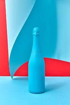 Composição criativa de férias com garrafa de champanhe pintada de azul sobre fundo duotônico com folha de papel azul encaracolado, copie o espaço.