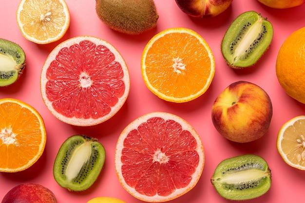 Composição criativa de frutas em rosa com sombras duras