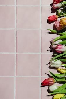Composição criativa de maquete de flores tulipa vermelha, branca e amarela em um fundo de piso de ladrilho rosa