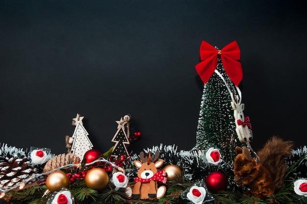 Composição criativa de natal e ano novo feita de árvore de natal e decorações com luz de natal e pinha com árvore de abeto na superfície escura vista frontal do conceito de natal