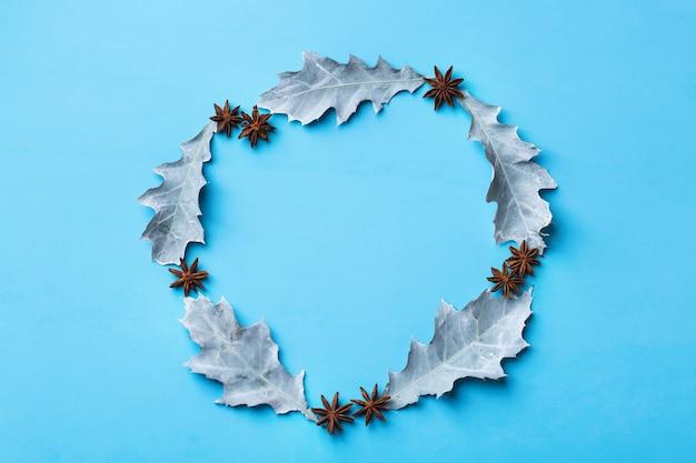 Composição criativa de natal inverno outono outono dia com folhas secas decorativas. camada plana, vista de cima, espaço de cópia, fundo pastel azul natureza morta para cartão de felicitações