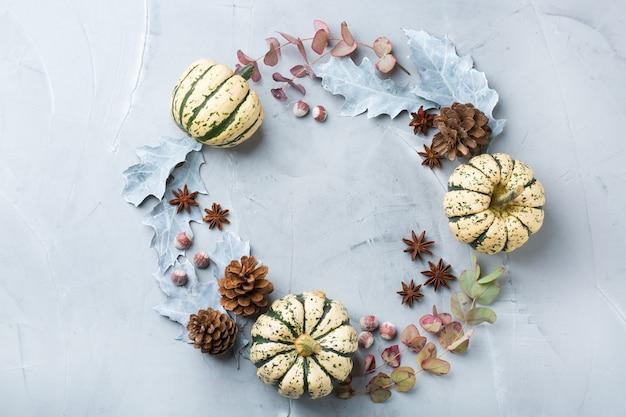 Composição criativa de natal inverno outono outono dia com folhas secas decorativas e abóboras brancas. camada plana, vista de cima, espaço de cópia, fundo pastel azul natureza morta para cartão de felicitações